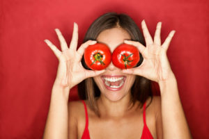 Laughing woman holding tomatoes over eyes
