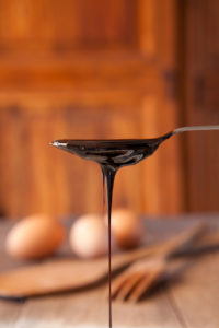 Molasses dripping from a spoon