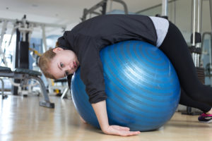 Bored woman laying on exercise ball