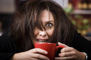 Woman with funny face holding a cup of coffee